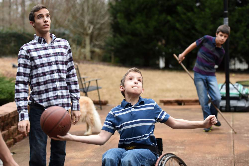 Zachary, who was also born with spina bifida, gets off a shot as his brothers Samuel and Ethan look on at their home in Villa Rica. Samuel and Zachary love to play basketball, but Ethan prefers Legos and Minecraft.